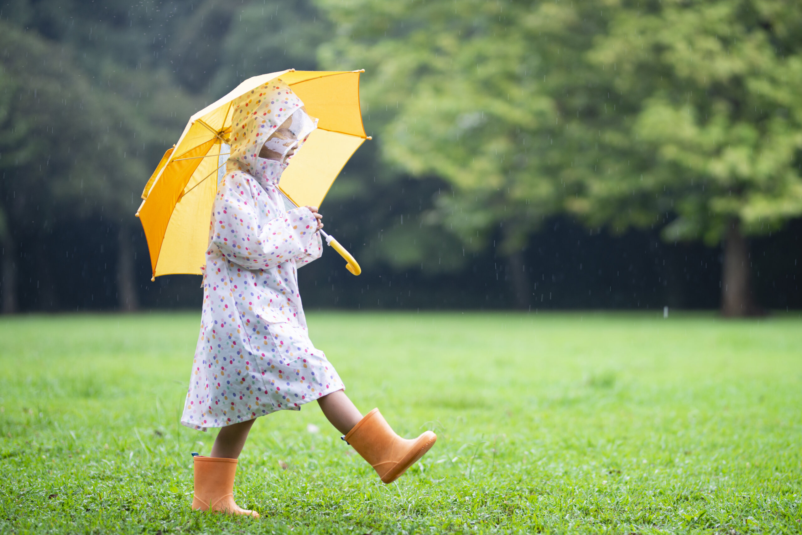 Person standing in the rain walking on grass with umbrella during summer showers.