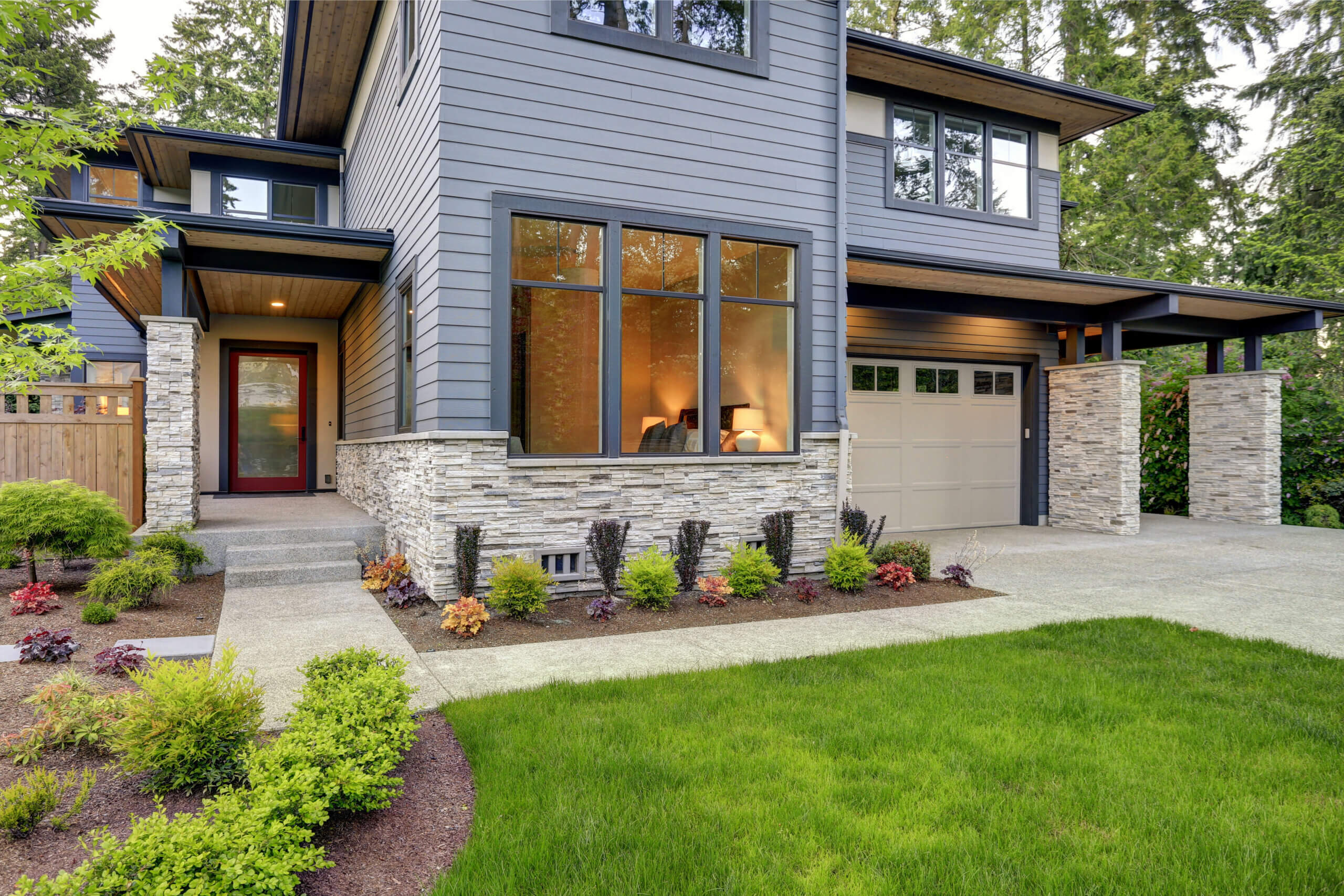 Luxurious new home with curb appeal. Trendy grey two-story exterior in Bellevue with large picture windows, stone foundation veneer, covered porch and concrete pathway. Northwest, USA